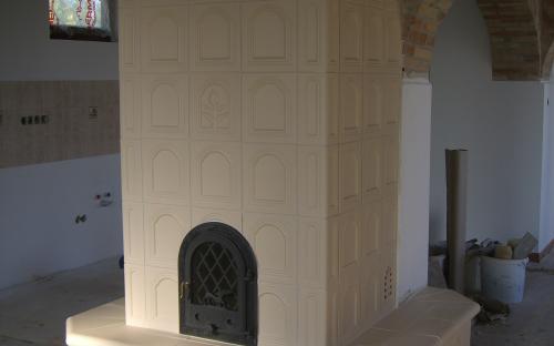 kémény köré épített kapus mintás cserépkályha a Nádasd Kerámiától bontott tégla talapzattal matt beige színben